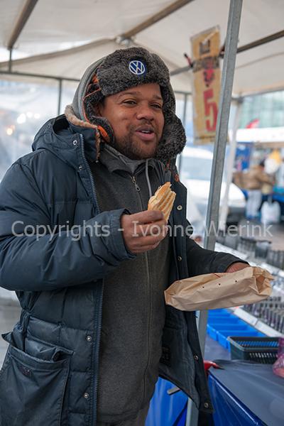 Allochtone man eet broodje