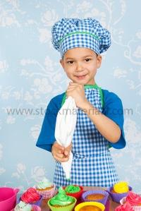 Little boy baking cupcakes