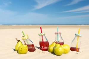 Bottles lemonade and fresh fruit at the beach