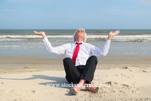 Senior business man sitting in meditation at the beach