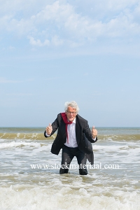 Senior business man standing in sea water