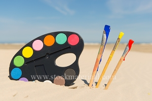 Colorful Painters palette with brushes at the beach